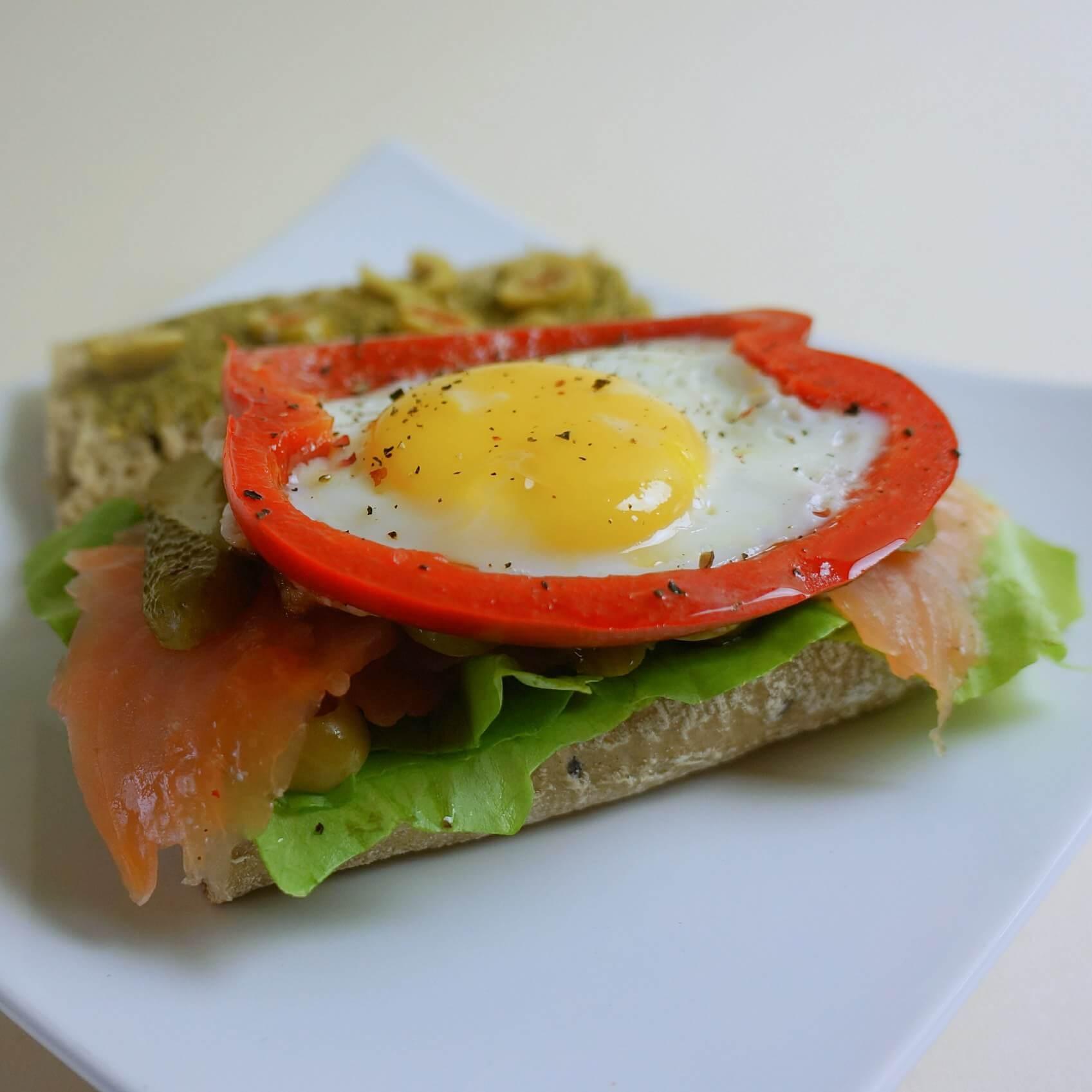 Pan łosoś z jajkiem, oliwkami i ogórkiem na połowie bagietki lekko posmarowanej bazyliowym pesto.